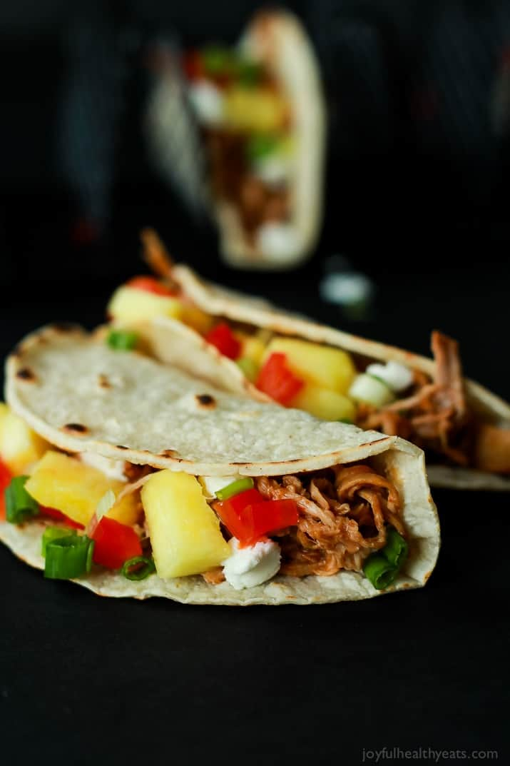 Two Hawaiian Pork Tacos filled with sweet pulled pork, fresh pineapple, red peppers, and goat cheese