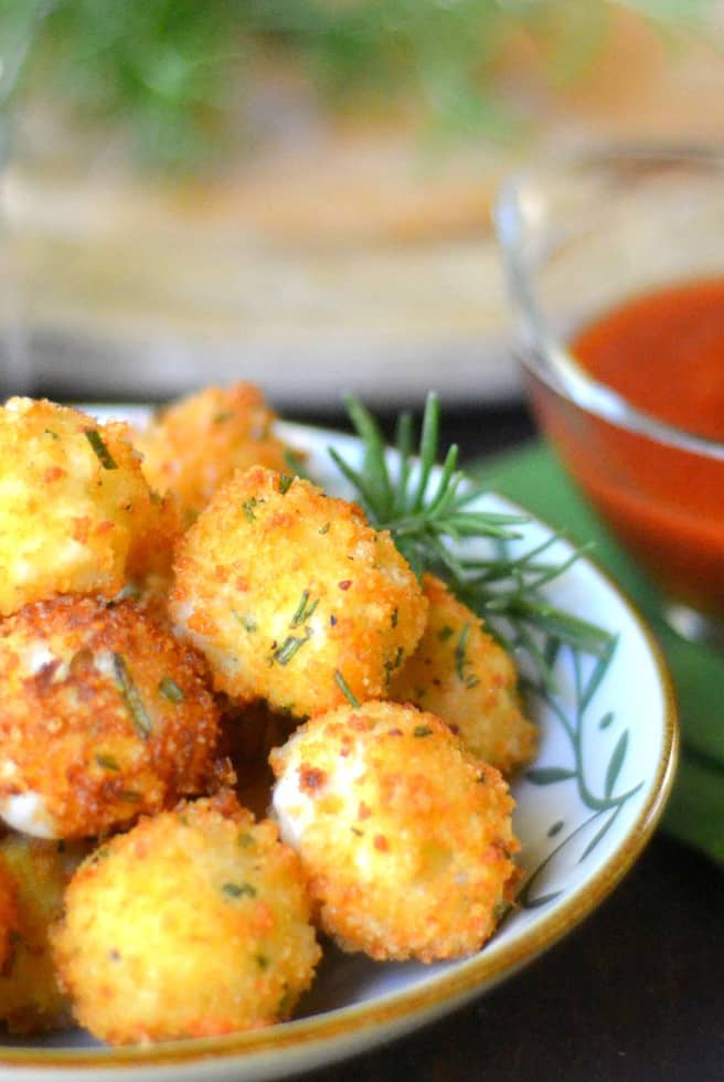A Bowl of Fried Rosemary Mozarella Balls with a Sprig of Rosemary