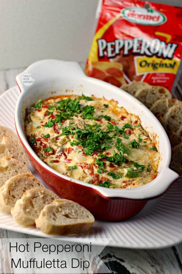 Hot Pepperoni Muffuletta Dip in a Red Crock with Slices of Bread on the Side