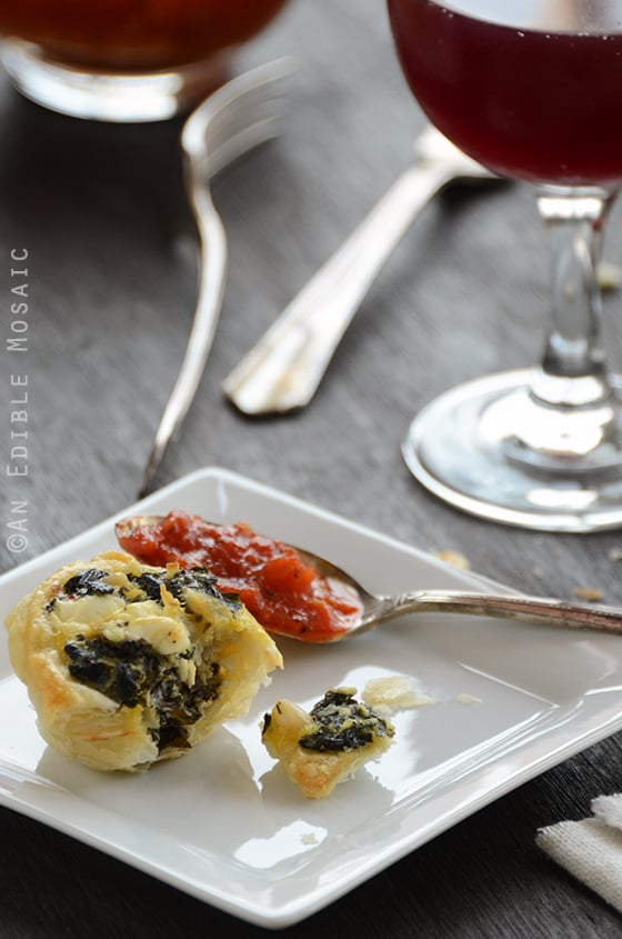 A Spanakopita Puff on a Square Plate Next to a Glass of Wine