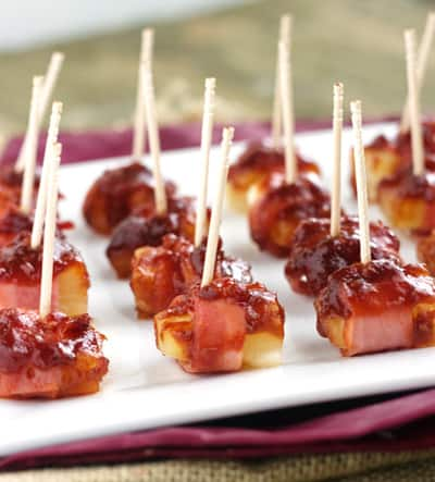 Sweet and Sower Bacon Wrapped Pineapple Pops on a Piece of Parchment Paper