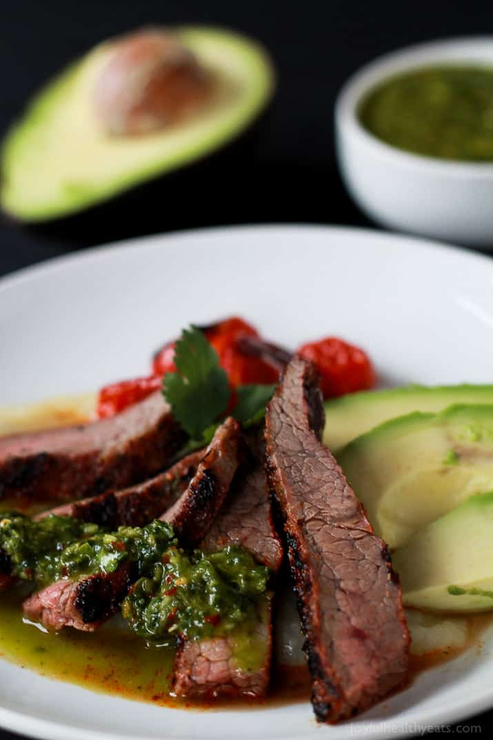 Close-up of sliced Chili Rubbed Flank Steak on a plate served with fresh chimichurri sauce and avocado