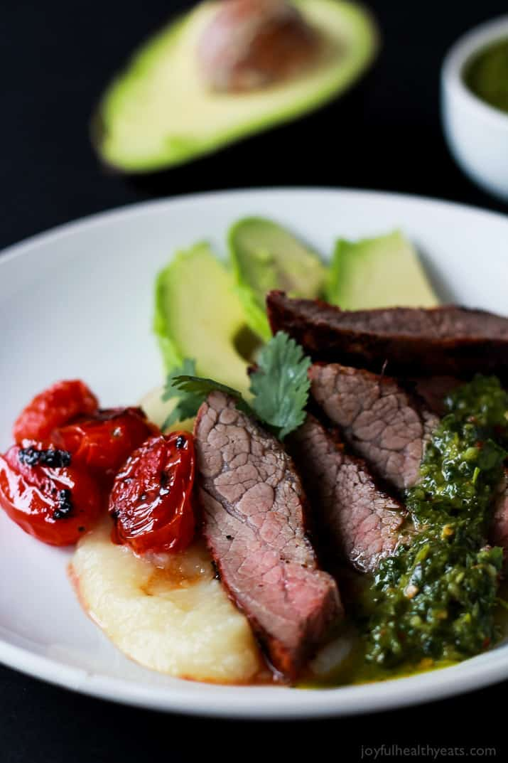 Close-up of Chili Rubbed Flank Steak slices on a plate served with fresh chimichurri sauce, roasted tomatoes, and fresh avocado