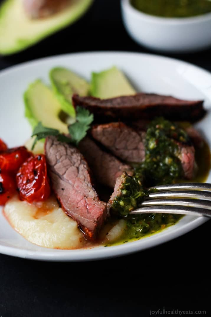 Close-up of slices of Chili Rubbed Flank Steak on a plate served with fresh chimichurri sauce, roasted tomatoes and fresh avocado