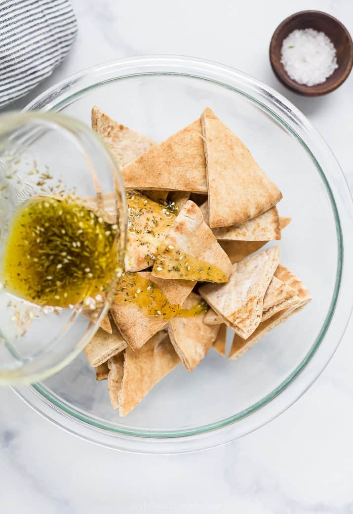 pouring herb olive oil mixture over pita chips