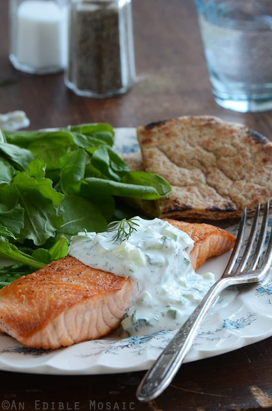 A Plate of Seared Salmon with Tzatziki Sauce, Spinach and Bread