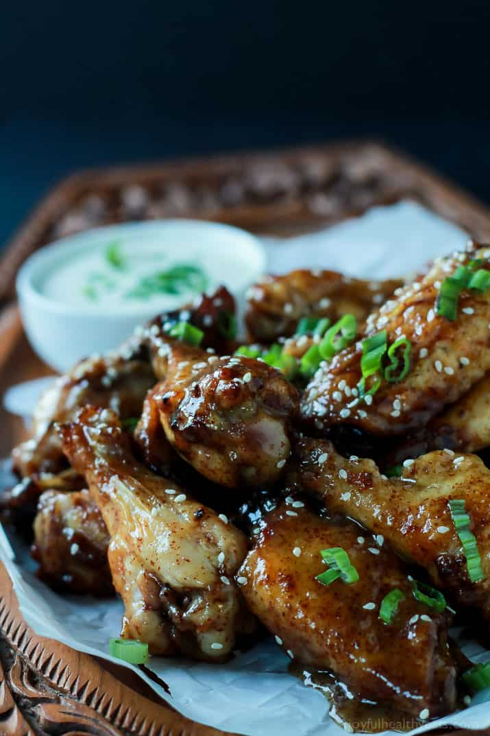 A pile of baked chicken wings with honey mustard dipping sauce