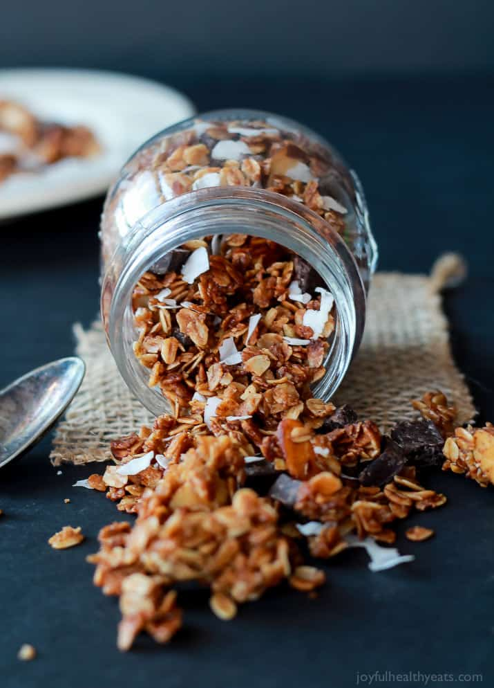 A Jar On its Side Pouring Out Homemade Almond Joy Granola