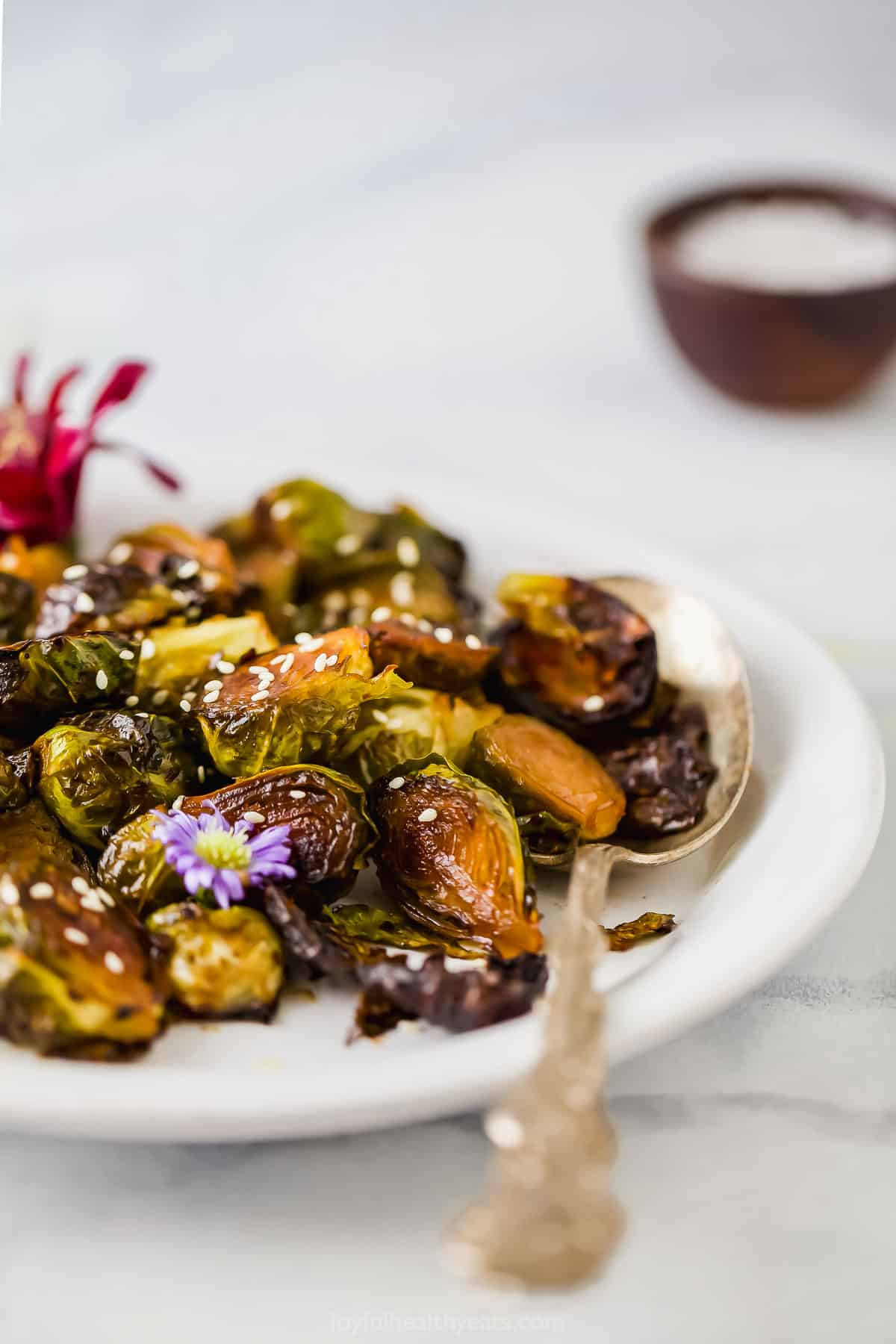 side view of honey soy roasted brussels sprouts with a spoon