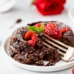 photo of half eaten nutella chocolate lava cake with chocolate oozing out topped with champagne muddled raspberries