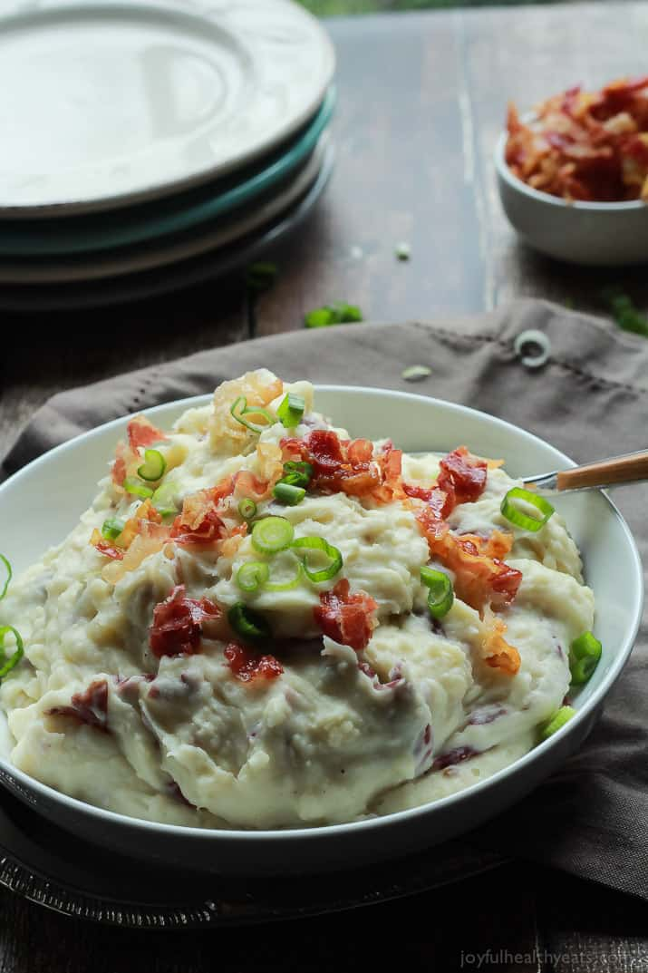 A bowl of Creamy Goat Cheese Horseradish Mashed Potatoes topped with crispy pancetta and fresh green onions