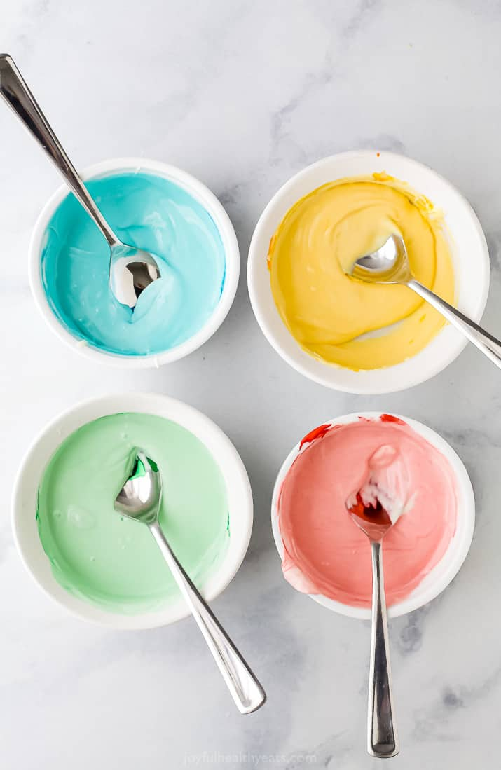 four bowls with pastel colored chocolates