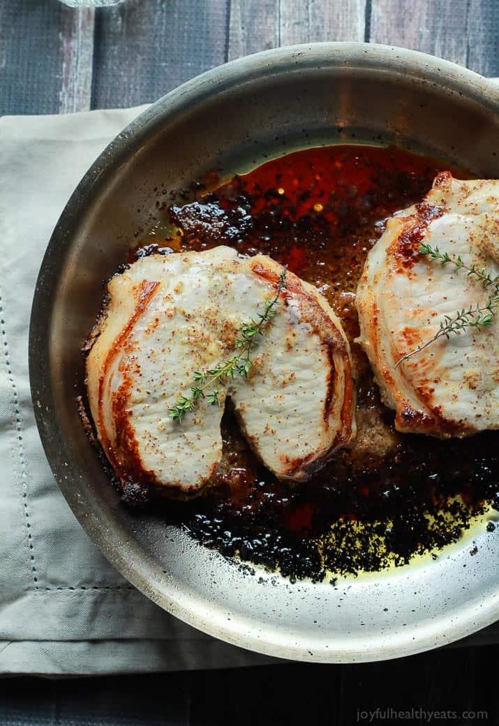 Two Juicy Pork Chops Searing in a Metal Skillet