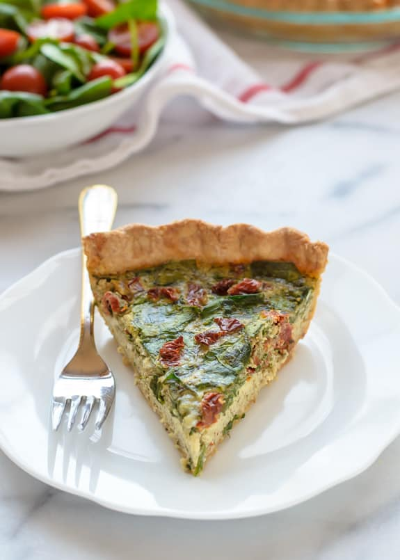 A Slice of Pesto Quiche with Sundried Tomatoes & Parmeson on a Plate with a Fork