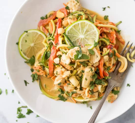 closeup photo of thai chicken zucchini noodles with spicy peanut sauce in a bowl
