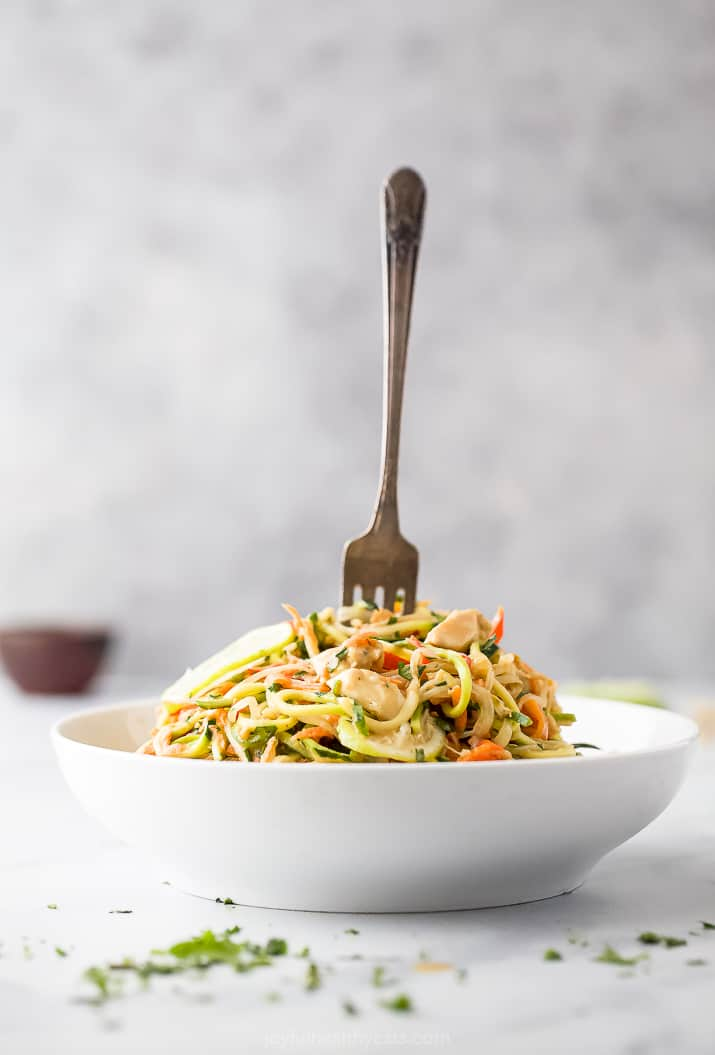 a bowl filled with thai chicken zucchini noodles and a fork in the bowl