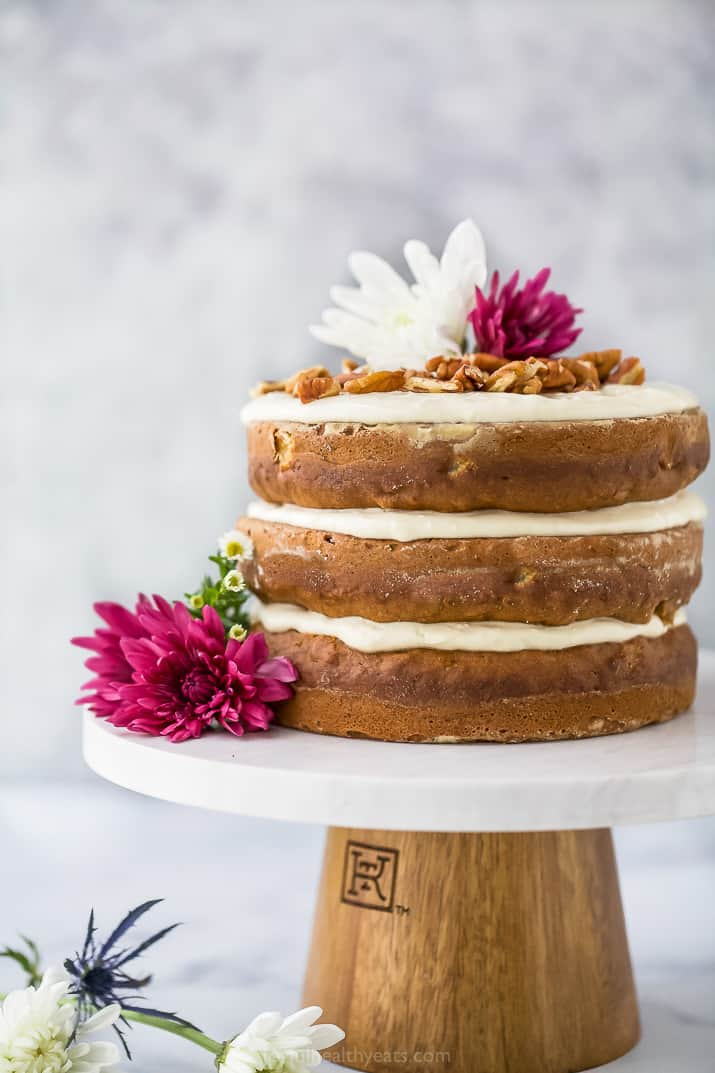 close up photo of The BEST Hummingbird Cake Recipe with Light Cream Cheese Frosting on a cake platter with flowers on top