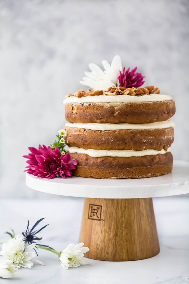 The BEST Hummingbird Cake Recipe with Light Cream Cheese Frosting on a cake platter with flowers