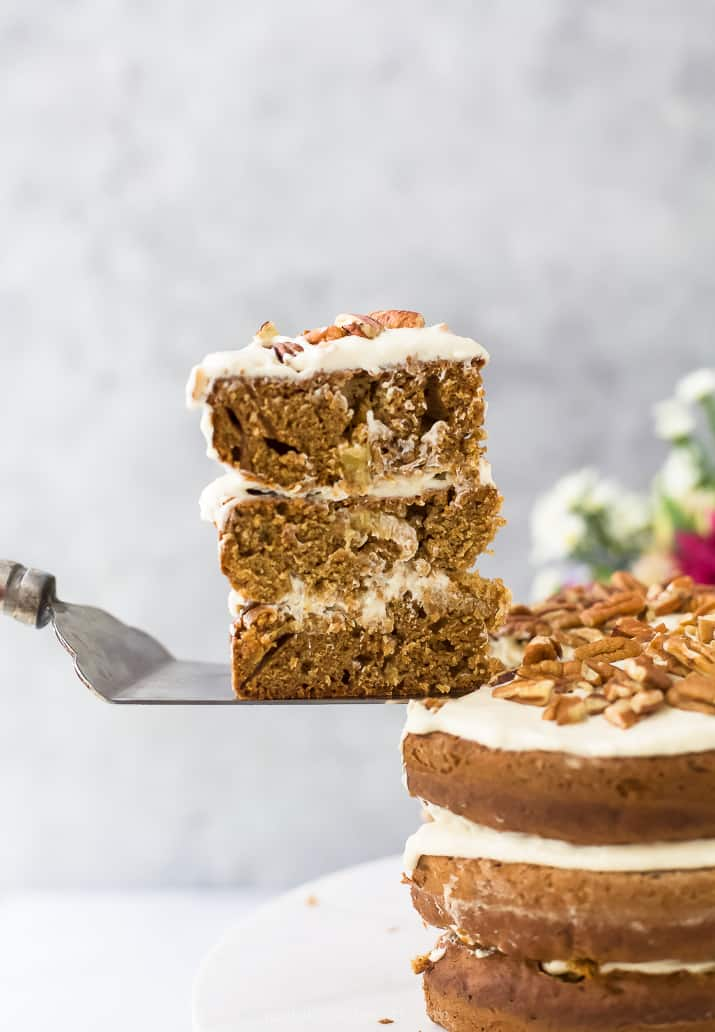 a slice of The BEST Hummingbird Cake Recipe with Light Cream Cheese Frosting being pulled out from the cake and ready to serve
