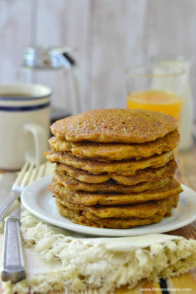 A Stack of Carrot Cake Pancakes Next to a Glass of Orange Juice