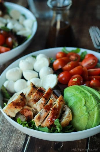 A Quick Easy Dinner for two, Avocado Caprese Chicken Salad topped with a light Balsamic Vinaigrette. The perfect Salad recipe for summer that only takes 15 minutes!   joyfulhealthyeats.com #recipe