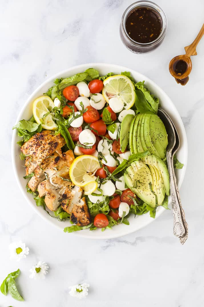 overhead photo of avocado caprese chicken salad in a bowl with balsamic vinaigrette