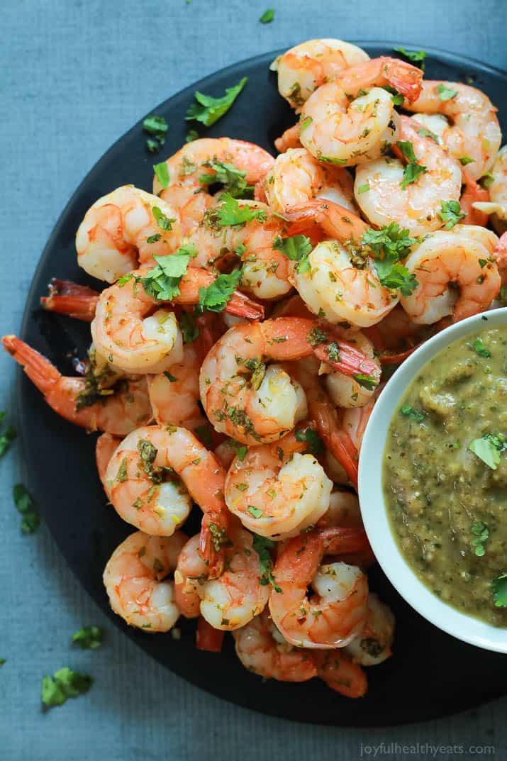 Top view of Cilantro Lime Roasted Shrimp on a plate with a cup of homemade Roasted Tomatillo Sauce