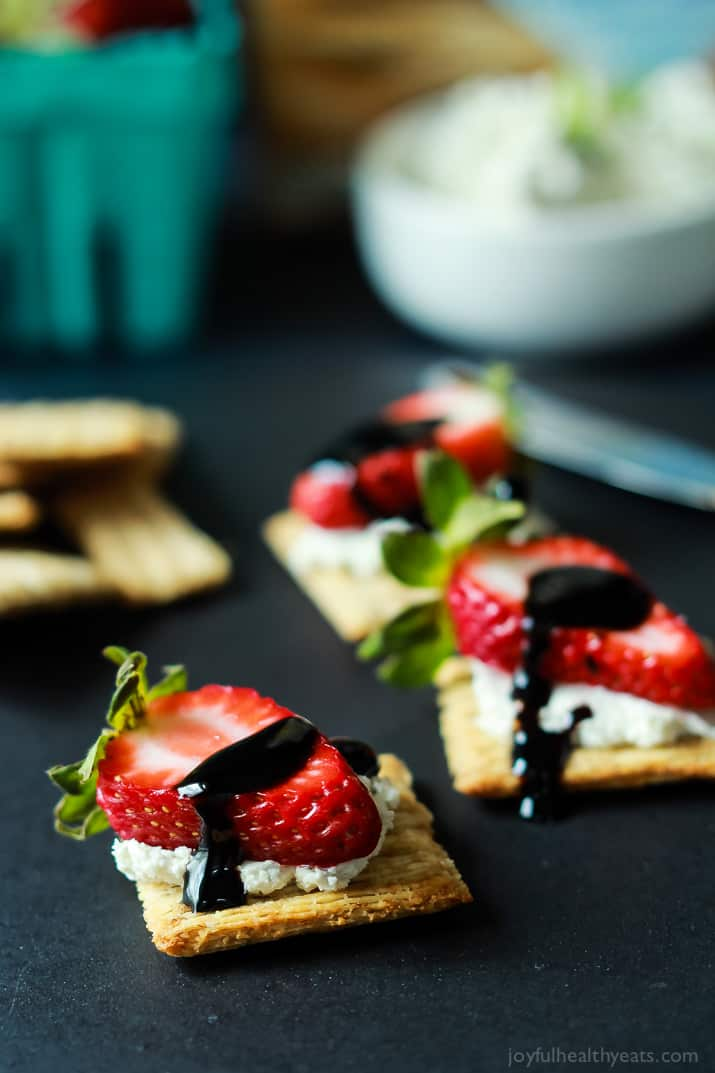 Strawberry Goat Cheese Bites on a cracker topped with a Balsamic Reduction Drizzle