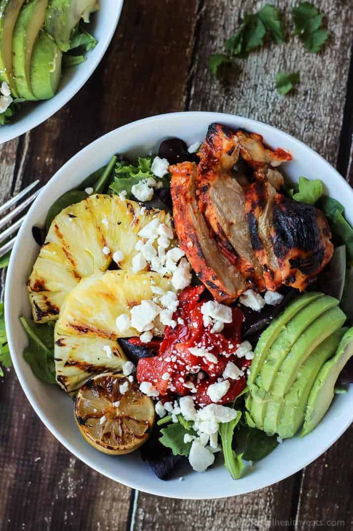 Top view of a bowl of Harissa Lime Grilled Chicken Salad with pineapple, avocado and crumbled feta