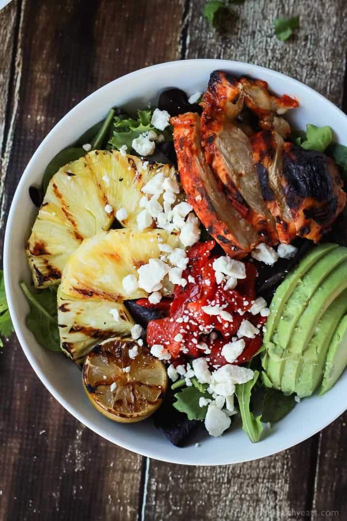 Top view of a bowl of Harissa Lime Grilled Chicken Salad with grilled pineapple, limes, and fresh avocado