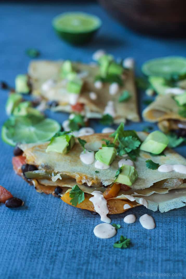 Easy Tex-Mex Vegetarian Crepe Quesadillas filled with fresh corn, bell peppers, black beans, and onions then topped with a drizzle of Chipotle Lime Crema! An appetizer that is to die for! | joyfulhealthyeats.com #recipes