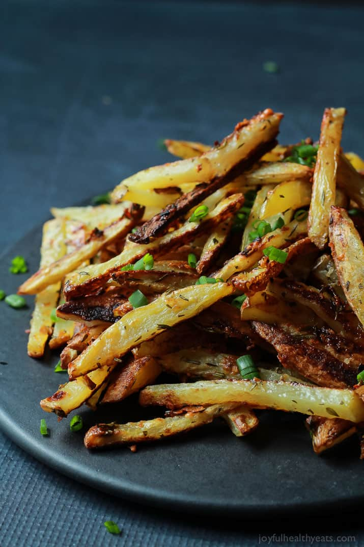Crispy Baked Garlic Parmesan Fries with scallions piled on a plate