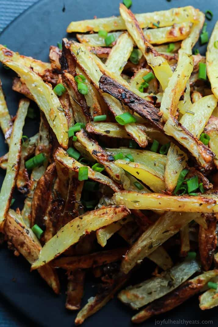 Top view of Crispy Baked Garlic Parmesan Fries garnished with scallions on a plate