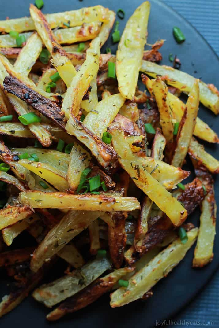 Top view of Crispy Baked Garlic Parmesan Fries with scallions on a plate