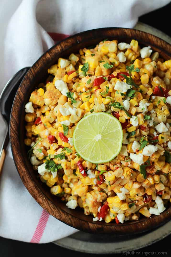 A big bowl of grilled corn salad with cheese, lime and peppers