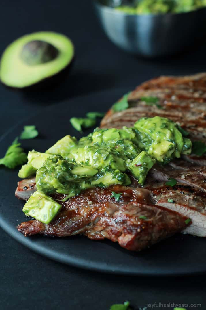 Grilled steak topped with fresh chimichurri sauce on a black plate