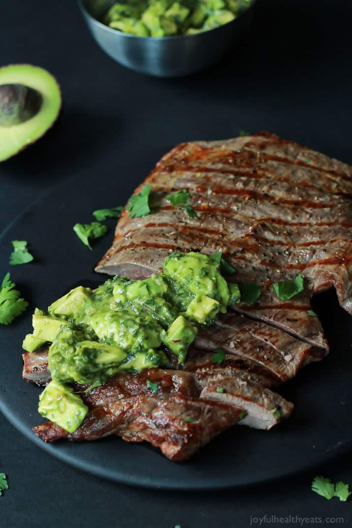 Sliced grilled Flank Steak with fresh Chimichurri sauce on a black plate