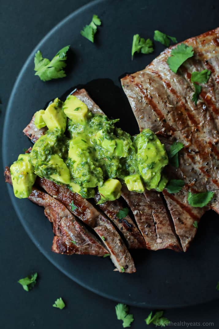 Top view of Grilled Flank Steak with Avocado Chimichurri on a black plate sprinkled with cilantro