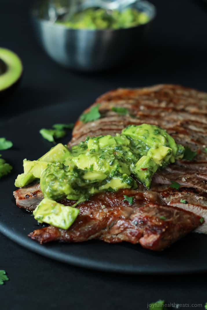 Sliced Flank Steak with Avocado Chimichurri on a black plate sprinkled with cilantro