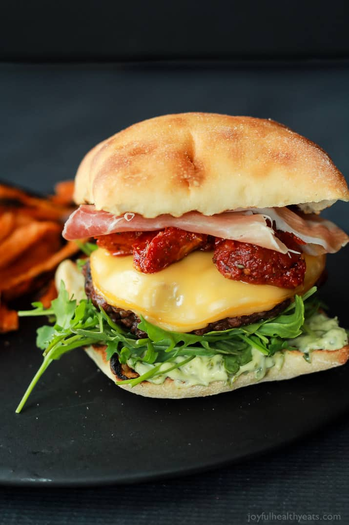 A juicy Italian Cheeseburger served on a toasted ciabatta bun, topped with smoked gouda cheese, spicy arugula, sun dried tomatoes, salty prosciutto, and basil pesto aioli! Done in 15 minutes this Burger is sure to be your new favorite this summer! | joyfulhealthyeats.com #recipes #grill #easy
