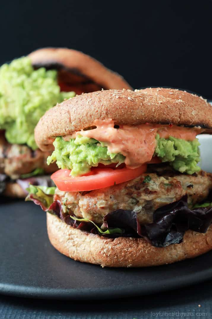 Healthy juicy Southwestern Turkey Burgers stuffed with lettuce, tomato, a simple guacamole, and a Spicy Aioli made with Piquillo Peppers and Chipotle Peppers! The ultimate Turkey Burger recipe your family will love - just 20 minutes! | joyfulhealthyeats.com #recipes #grill
