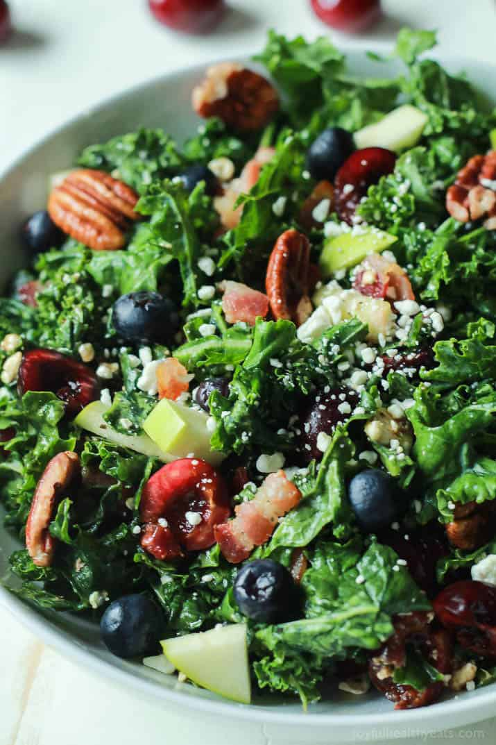 Close-up of Summer Kale Salad with fresh cherries and blueberries, pecans, bacon and feta in a serving bowl