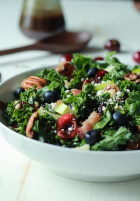 A Summer Kale Salad Recipe that will blow your mind! Filled with fresh cherries and blueberries for some sweet then countered with salty bacon and feta. Perfect for a backyard bbq party this summer, its even Red White and Blue! | joyfulhealthyeats.com #recipe
