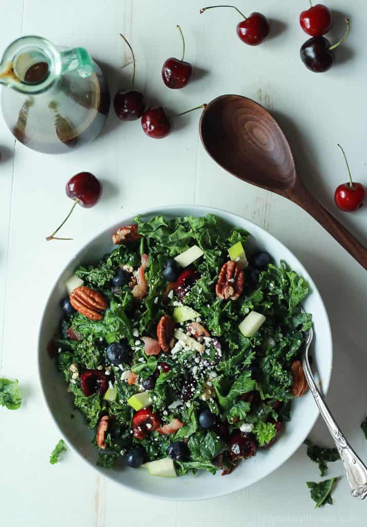 Top view of Summer Kale Salad next to balsamic vinaigrette and fresh cherries
