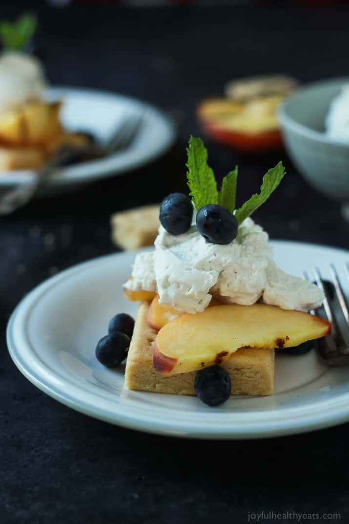 Grilled Peach Shortcake with buttery shortbread, grilled peaches, and coconut whipped cream on a plate