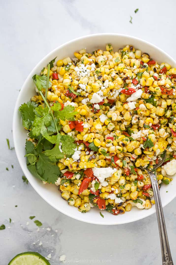 spoon scooping some summer corn salad out of a bowl