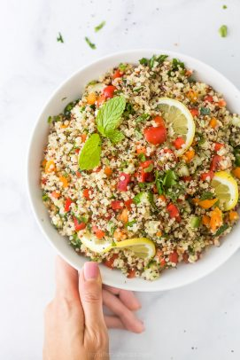 20 minute quinoa tabbouleh salad in a bowl with a hand holding the bowl