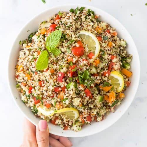 20 minute quinoa tabbouleh salad in a bowl with a hand on the bowl
