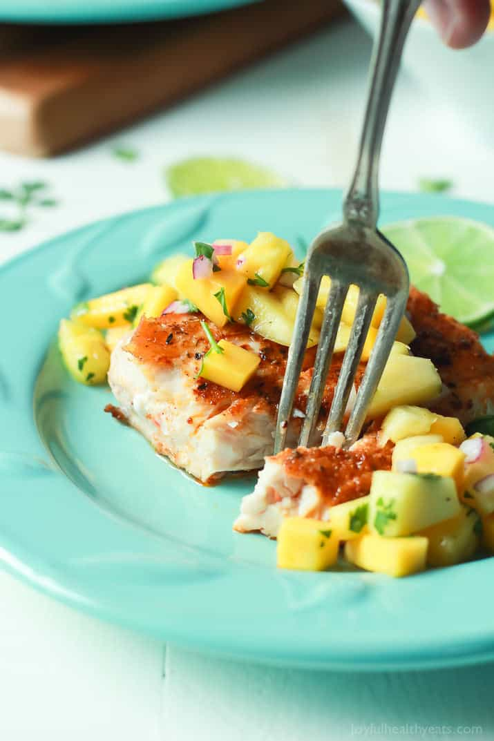 A fork spearing Pan Seared Cajun Mahi Mahi with a fresh Mango Pineapple Salsa on a plate