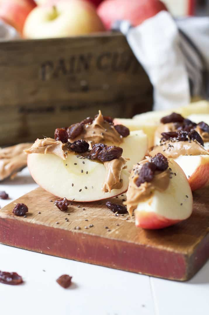 Apple wedges with peanut butter, dried cranberries, and chia seeds on a wooden cutting board